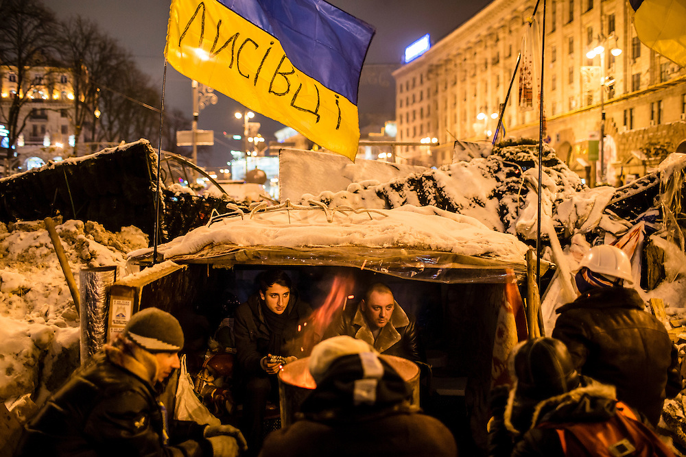 KIEV, UKRAINE - DECEMBER 11: Anti-government protesters huddle under a makeshift shelter built into a barricade to block the street near Independence Square on December 11, 2013 in Kiev, Ukraine. Thousands of people have been protesting against the government since a decision by Ukrainian president Viktor Yanukovych to suspend a trade and partnership agreement with the European Union in favor of incentives from Russia. (Photo by Brendan Hoffman/Getty Images) *** Local Caption ***