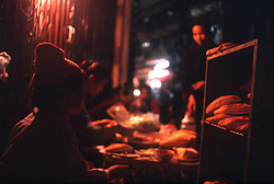 Color film photograph of street shop selling bread at night in Hanoi's Old Quarter, Vietnam, Southeast Asia