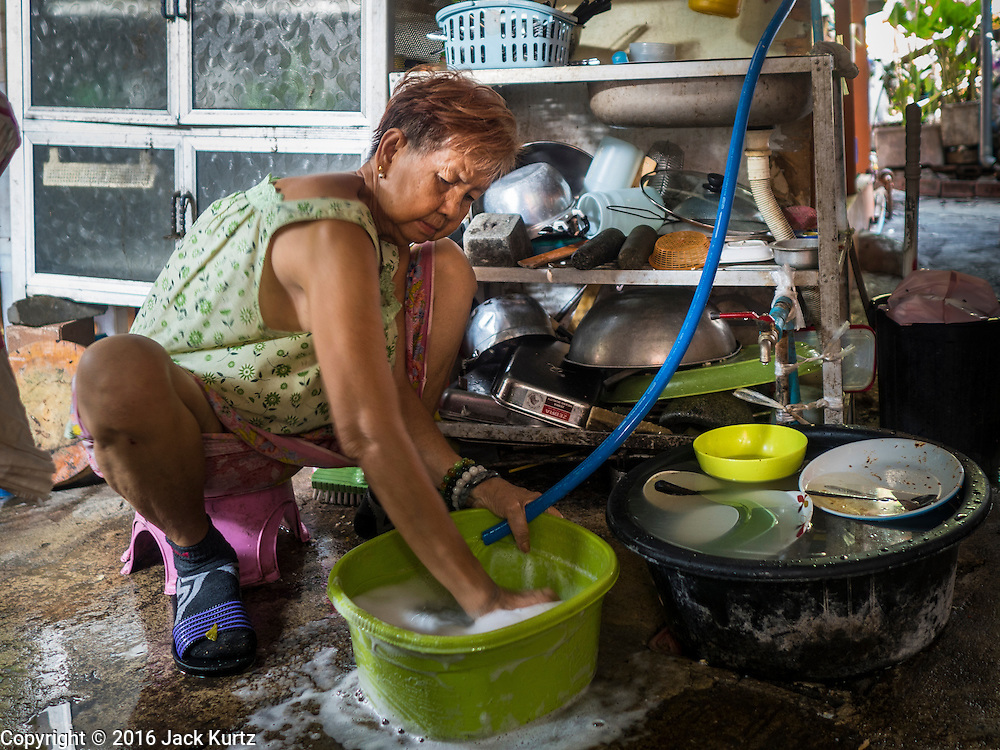 07 APRIL 2016 - BANGKOK, THAILAND: A woman does her dishes on a sidewalk in the squatters' community in Mahakan Fort. Mahakan Fort was built in 1783 during the reign of Siamese King Rama I. It was one of 14 fortresses designed to protect Bangkok from foreign invaders, and only of two remaining, the others have been torn down. A community developed in the fort when people started building houses and moving into it during the reign of King Rama V (1868-1910). The land was expropriated by Bangkok city government in 1992, but the people living in the fort refused to move. In 2004 courts ruled against the residents and said the city could take the land. The final eviction notices were posted last week and the residents given until April 30 to move out. After that their homes, some of which are nearly 200 years old, will be destroyed.       PHOTO BY JACK KURTZ