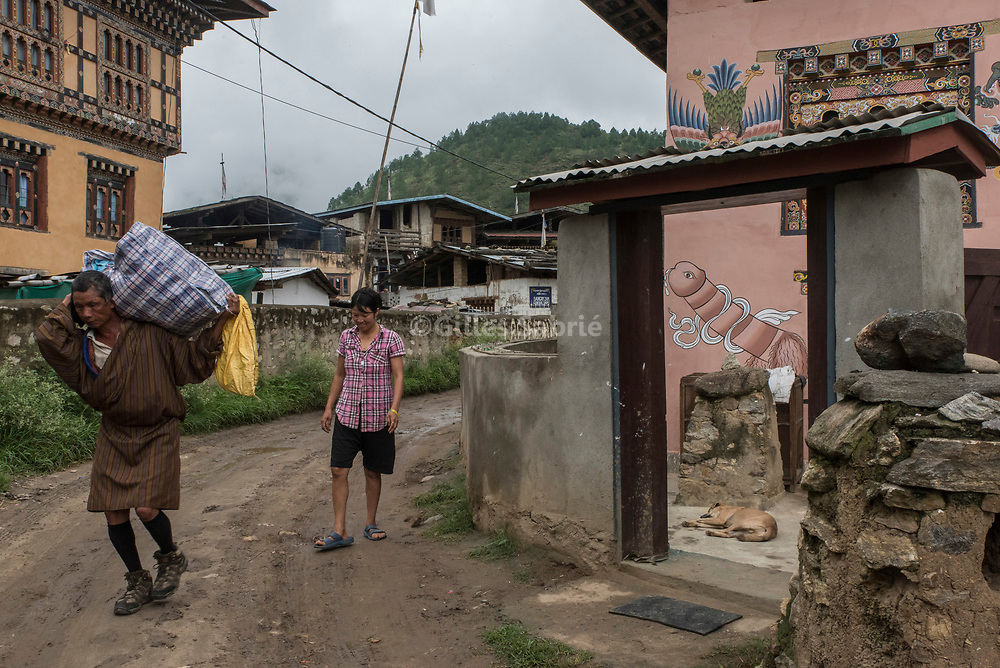 For a story by Steven Lee Myers, Bhutan<br /> Lobesa, Bhutan, August 2nd, 2017<br /> Locals walking by a  traditional Bhutanese house decorated with elaborate paintings of mythical animals and that of a penis. Locals believe that the phallic symbols bring good luck and drives away evil spirits, Its origin can be found in the Bon religion that predated the advent of Tibetan Buddhism. Phallus representations are also linked to the XVIth century Lama Drukpa Kunley  popularly known as the &ldquo;Divine Madman&rdquo; for his unorthodox ways of teaching, and for his bizarre and shocking behaviours.<br /> Gilles Sabri&eacute; pour The New York Times