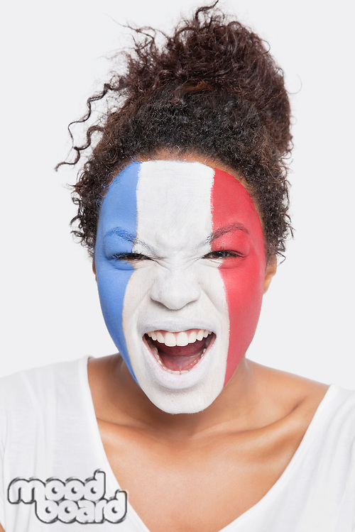 Portrait of angry young African American woman with French flag painted on face shouting against white background