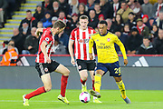 Arsenal midfielder Joe Willock (28) on the ball watched closely by Sheffield United defender Chris Basham (6) during the Premier League match between Sheffield United and Arsenal at Bramall Lane, Sheffield, England on 21 October 2019.