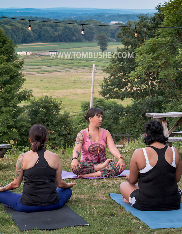 Westtown, New York - Elisa Piscitelli of Wild Soul Yoga Studio leads a sunset yoga session at Westtown Brew Works on July 21, 2016.