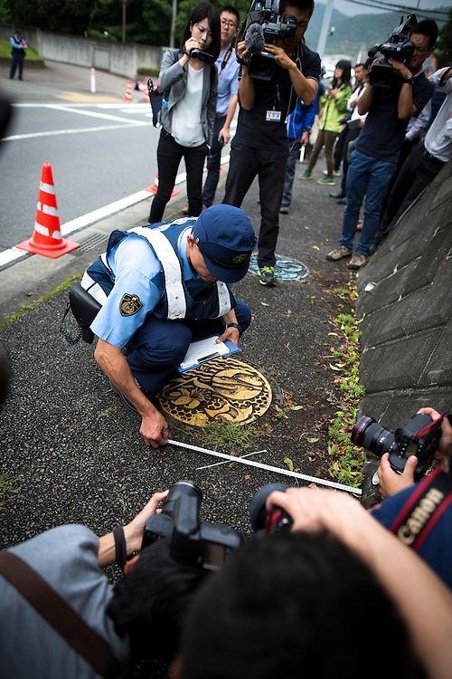 SAGAMIHARA, JAPAN - JULY 27 :  Police investigators measuring the distance of a found object from the wall, dropped by the suspect in front of the entrance of Tsukui Yamayuri-en building at Sagamihara on Wednesday, July 27, 2016 in Kanagawa prefecture, Japan. Police arrested 26 year old Satoshi Uematsu after breaking inside the building facility for handicapped and killing 19 people and injuring 20 in the city of Sagamihara, west of Tokyo. (Photo: Richard Atrero de Guzman/NURPhoto)