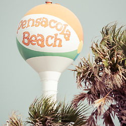 Beach ball water tower and plam trees Pensacola Beach Florida retro photo. Pensacola Beach is a coastal city on Santa Rosa Island in the Emerald Coast of the Southeastern United States of America. Photo is vertical and high resolution. Copyright ⓒ 2018 Paul Velgos with All Rights Reserved.