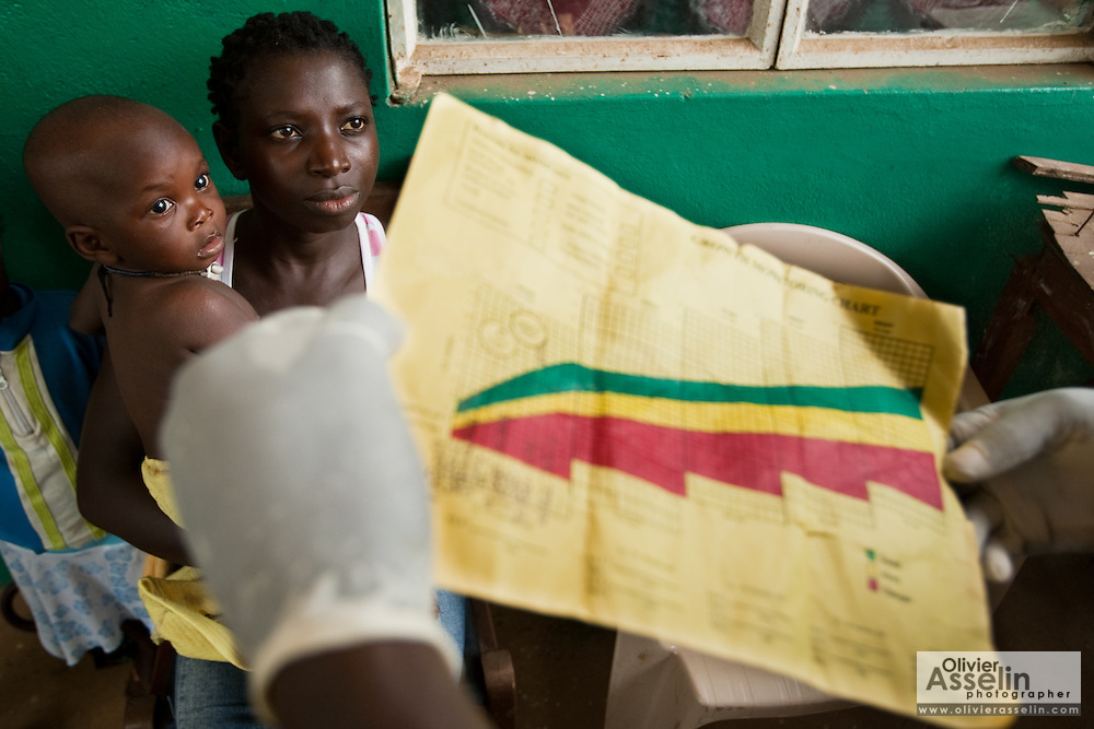 A woman holds her child while vaccinator Samuel Yambasu holds up the child's health card at the Gbondapi community health center in the village of Gbondapi, Sierra Leone on Friday March 19, 2010..