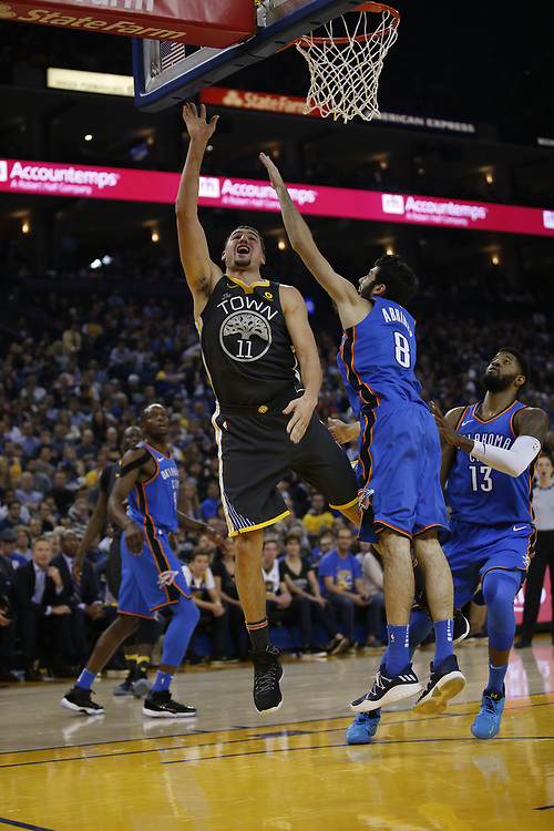 Golden State Warriors guard Klay Thompson (11) lays up a shot during the first half of an NBA game between the Warriors and Oklahoma City Thunder at Oracle Arena, Tuesday, Feb. 6, 2018, in Oakland, Calif.