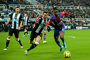 Wilfried Zaha (#11) of Crystal Palace battles for possession of the ball with Javi Manquillo (#19) of Newcastle United during the Premier League match between Newcastle United and Crystal Palace at St. James's Park, Newcastle, England on 21 December 2019.