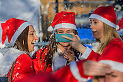 The finish brings relief and a shower of 'snow' selfies are obligatory - Thosuands of runners, of all ages, in santa suits and other Christmas costumes runaround Clapham Common for Great Ormond Street Hospital and for fun. London 30 Nov 2016