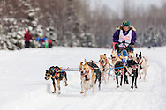 Musher Roxy Wright competing in the Fur Rendezvous World Sled Dog Championships at Campbell Airstrip in Anchorage in Southcentral Alaska. Winter. Afternoon.
