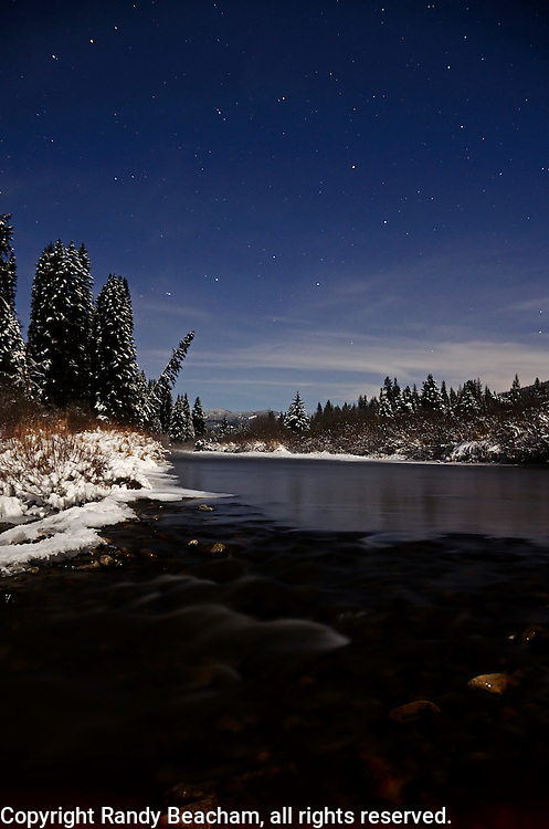 The Yaak River and Big Dipper at night during a full moon in winter. Yaak Valley, Montana.