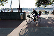 Een vrouw fietst met een kind achterop langs de kade in Keulen.<br /> <br /> A woman is cycling with a child at Cologne.