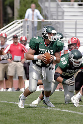 09 September 2006  Titan quarterback Brandon Cotter drops and looks for a receiver..In the first ever football competition between the Olivet Comets and the Illinois Wesleyan Titans, the Titans strut off the field with a 21- 6 victory. .Game action took place at Wilder Field on the campus of Illinois Wesleyan University in Bloomington Illinois.