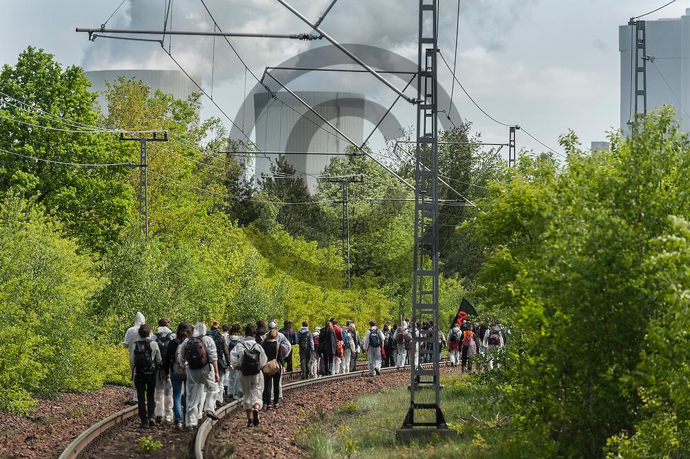 Aktivisten laufen am 14.05.2016 in Schwarze Pumpe, Deutschland &uuml;ber die Bahnschienen in Richtung blockade. Mehrere Tausend Aktivisten blockieren den Braunkohlentagebau und die Zufahrtswege zum Kohlekraftwerk Schwarze Pumpe (im Hintergrund) um gegen die Nutzung von fossilen Brennstoffen zu protestieren. Foto: Markus Heine / heineimaging<br /> <br /> <br /> <br /> <br /> ------------------------------<br /> <br /> Ver&ouml;ffentlichung nur mit Fotografennennung, sowie gegen Honorar und Belegexemplar.<br /> <br /> Bankverbindung:<br /> IBAN: DE65660908000004437497<br /> BIC CODE: GENODE61BBB<br /> Badische Beamten Bank Karlsruhe<br /> <br /> USt-IdNr: DE291853306<br /> <br /> Please note:<br /> All rights reserved! Don't publish without copyright!<br /> <br /> Stand: 05.2016<br /> <br /> ------------------------------ am 14.05.2016 bei Spremberg, Deutschland. Mehrere Tausend Aktivisten blockieren den Braunkohlentagebau und die Zufahrtswege zum Kohlekraftwerk Schwarze Pumpe um gegen die Nutzung von fossilen Brennstoffen zu protestieren Foto: Markus Heine / heineimaging<br /> <br /> <br /> <br /> <br /> ------------------------------<br /> <br /> Ver&ouml;ffentlichung nur mit Fotografennennung, sowie gegen Honorar und Belegexemplar.<br /> <br /> Bankverbindung:<br /> IBAN: DE65660908000004437497<br /> BIC CODE: GENODE61BBB<br /> Badische Beamten Bank Karlsruhe<br /> <br /> USt-IdNr: DE291853306<br /> <br /> Please note:<br /> All rights reserved! Don't publish without copyright!<br /> <br /> Stand: 05.2016<br /> <br /> ------------------------------