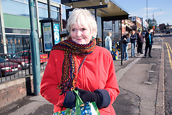 Older woman waiting at the bus stop,