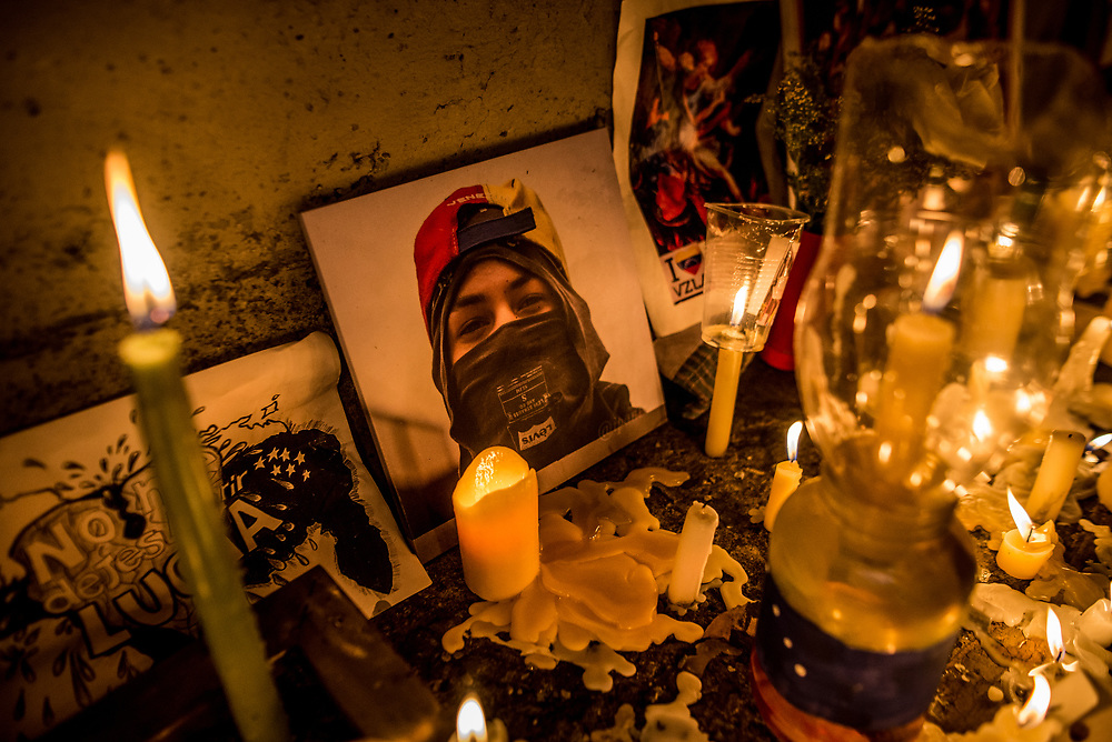 "CARACAS, VENEZUELA - JUNE 8, 2017: A photo of Neomar Lander, 17, is surrounded by candles and momentos that members of ""The Resistance"" made around the blood-stained spot on the road where Mr. Lander, was killed by security forces during a protest in Caracas. Johan Caldera, a close friend of Mr. Lander said he is even more determined to protest since his friend was killed.  ""Now, I have no fear - because I already lost the fear I had, and the respect for the military. The little respect I had, is gone. Now, the real soldiers of Venezuela wear rags on their faces, they wear a glove and they they don't use grenades - they use stones, they use their will, and they use their balls to go out into the street."" He said he had discussed with Neomar the possibility of being killed during the protests, ""and he [Neomar] told me: brother, if I die - if I lose my life during a protest, I don't want everyone to stop marching, I want them to march double and keep going to the street for a week, every single day, day and night without fear.""  PHOTO: Meridith Kohut"
