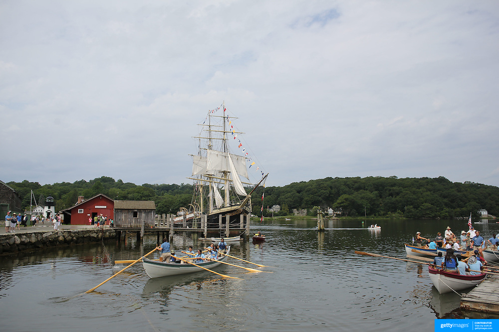 A whale boat parade passes the Joseph Conrad, the full- rigged ship moored on the historic waterfront at Mystic seaport. Mystic, Connecticut. 21st July 2013. Photo Tim Clayton