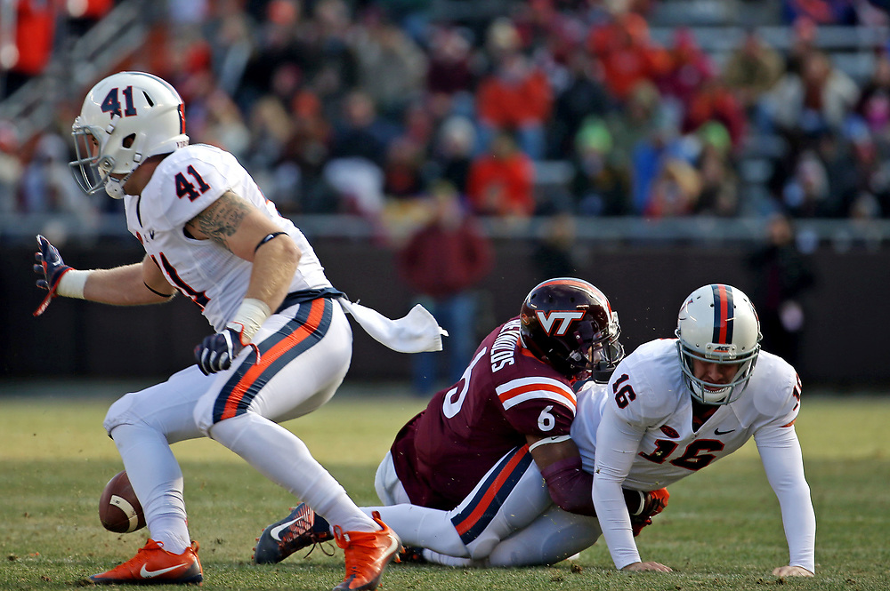 Nov 26, 2016; Blacksburg, VA, USA;  Virginia Cavaliers quarterback Connor Brewer (16) fumbles the ball against being hit by Virginia Tech Hokies safety Mook Reynolds (6) during the third quarter at Lane Stadium. Mandatory Credit: Peter Casey-USA TODAY Sports
