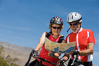 Senior couple with bikes reading map