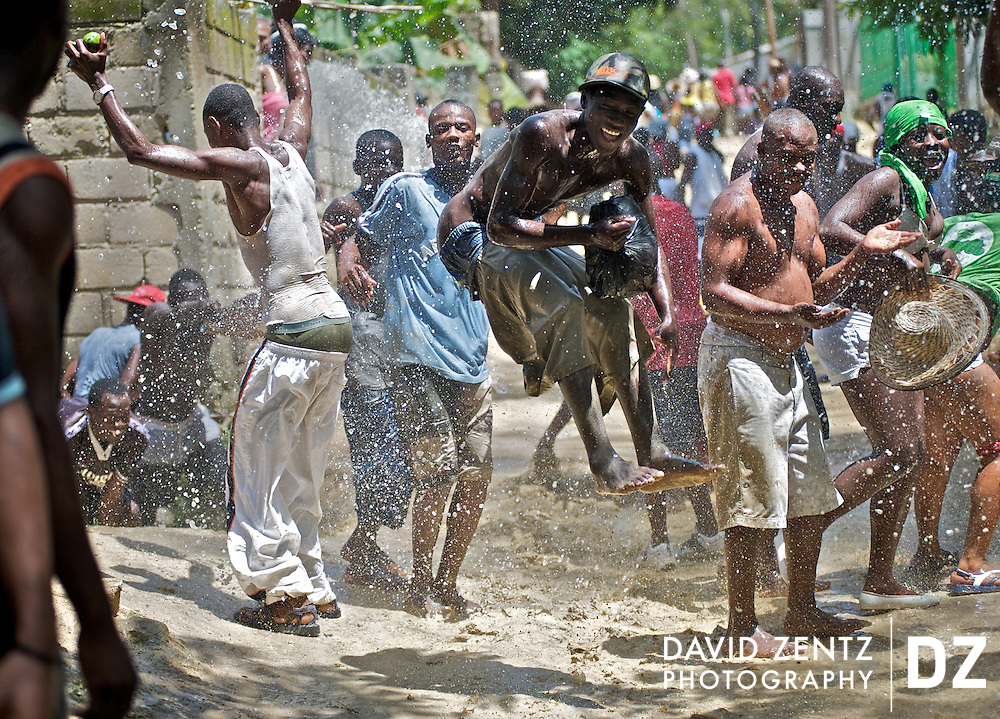 Members of a rara band known for splashing water live up to their reputation while making their way through the village of Ville Bonheur, Haiti, during the Saut D'eau voodoo festival on July 16, 2008. Rara bands are traditional peasant bands comprised of numerous people playing homemade instruments.