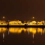 Lights and houses reflected in the calm waters of the Ahuriri Estuary. Ahuriri Estuary, Napier, New Zealand. September.