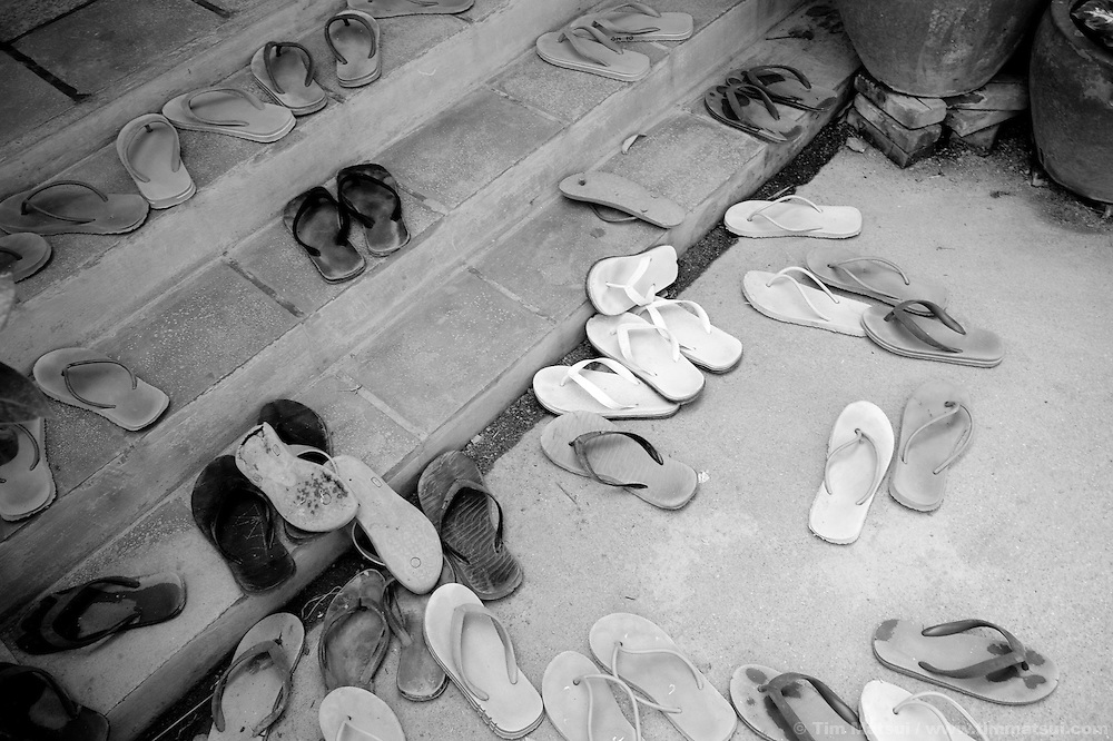"Young women's footwear at lunch time at Tom Dy, a residential facility run by the non governmental organization ""Acting for Women in Distressing Situations"" (AFESIP) on the outskirts of Phnom Penh, Cambodia. Tom Dy offers housing, education, training, and counseling for women who are victims of sex trafficking, worked as prostitutes, or are escaping domestic violence. Founded by Somaly Mam, who herself was once a prostitute and victim of trafficking and domestic abuse, AFESIP has three facilities in Cambodia and works with other NGO's to provide long term care for the women...The classroom instructor (white sleeve) is Touch Samol."
