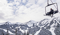 A skier sitting on a chairlift above Crystal Mountain Resort, Washington State, USA.