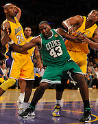 Celtics Kendrick Perkins comes down in an bad postition between Lakers Kobe Bryant and Andrew Bynum, causing an injury in the 2nd quarter. The Lakers defeated the Boston Celtics in game 6 of the NBA Finals 89-67. Los Angeles, CA 06/15/2010 (John McCoy/Staff Photographer).