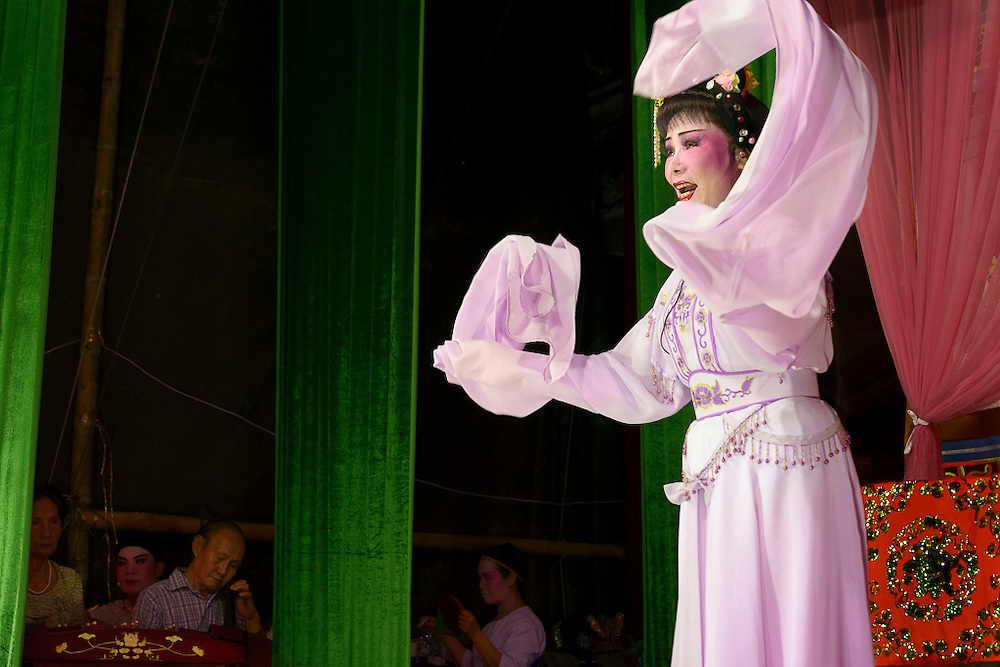 A singer from the Nam Sin Opera Company is performing on stage.