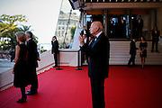 Gil Jacob prend des photos avec son téléphone sur le tapis rouge pendant le Festival de Cannes
