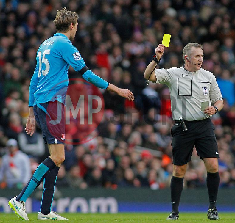 referee Jon Moss shows a yellow card to Stoke's Peter Crouch - Photo mandatory by-line: Mitchell Gunn/JMP - Mobile: 07966 386802 - 11/01/2015 - SPORT - football - London - Emirates Stadium - Arsenal v Stoke - Barclays Premier League