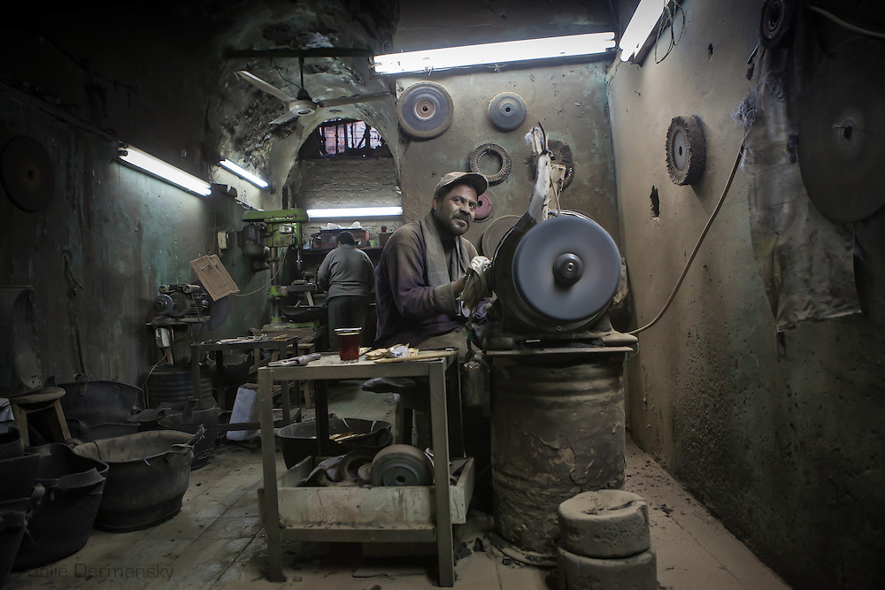 Sayed Hamid, a metal worker grinding metal in Islamic Cairo where craftsmen work in small workshops off the main street in Al-Darb Al-Ahmr. Many Egyptian craftsmen have degrees in higher education but couldn't find jobs in their fields.  Unemployment and lack of opportunity for advancement are factors that contributed to the discontent in Egypt leading to the January 25th revolution that toppled Mubarak's oppressive regime.