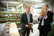 CDA minister Ab Klink (rechts) krijgt uitleg over het maken van schoenen van Reynier van Bommel tijdens zijn bezoek bij schoenenfabrikant Van Bommel.