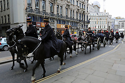 © Licensed to London News Pictures. 30/11/2013. Sacred soil from the battlefields of Flanders has been carried through the streets of London on a gun carriage. The soil arrived yesterday on a Belgian frigate and was loaded on to a gun carriage this morning. The gun carriage was drawn by six colour matched black Irish Draught horses and was taken to Wellington Barracks. It is pictured here entering Fleet Street in the City of London. Credit : Rob Powell/LNP