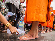 "22 JULY 2013 - PHRA PHUTTHABAT, THAILAND: A woman washes a monk feet during the Tak Bat Dok Mai at Wat Phra Phutthabat in Saraburi province of Thailand, Monday, July 22. Wat Phra Phutthabat is famous for the way it marks the beginning of Vassa, the three-month annual retreat observed by Theravada monks and nuns. The temple is highly revered in Thailand because it houses a footstep of the Buddha. On the first day of Vassa (or Buddhist Lent) people come to the temple to ""make merit"" and present the monks there with dancing lady ginger flowers, which only bloom in the weeks leading up Vassa. They also present monks with candles and wash their feet. During Vassa, monks and nuns remain inside monasteries and temple grounds, devoting their time to intensive meditation and study. Laypeople support the monastic sangha by bringing food, candles and other offerings to temples. Laypeople also often observe Vassa by giving up something, such as smoking or eating meat. For this reason, westerners sometimes call Vassa the ""Buddhist Lent.""     PHOTO BY JACK KURTZ"