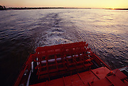 The Mississippi Queen paddlewheeler departing at sunset.