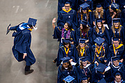 Two students exchange high fives at the 2017 undergraduate commencement ceremony on May 14 at the Spokane Veterans Memorial Arena.