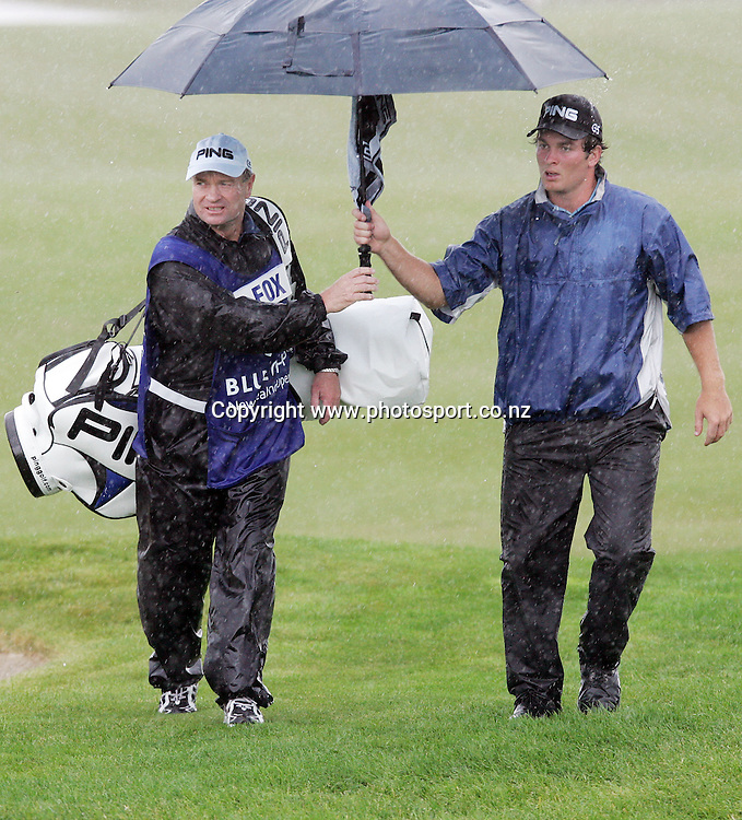 Former All Black Grant Fox (Ryan Fox's father and caddy) shelters himself and Ryan Fox from the rain during day one of the Blue Chip New Zealand Golf Open at Gulf Harbour, Whangaparoa, New Zealand on Thursday 30 November 2006. Photo: Hannah Johnston/PHOTOSPORT<br /><br /><br /><br />301106