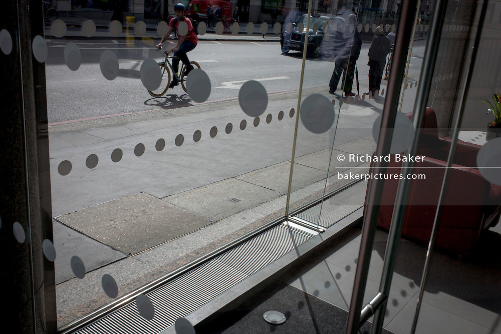 A cyclist pedals past an office foyer entrance featuring dots and circles (and shadows) on exterior windows in the City of London.