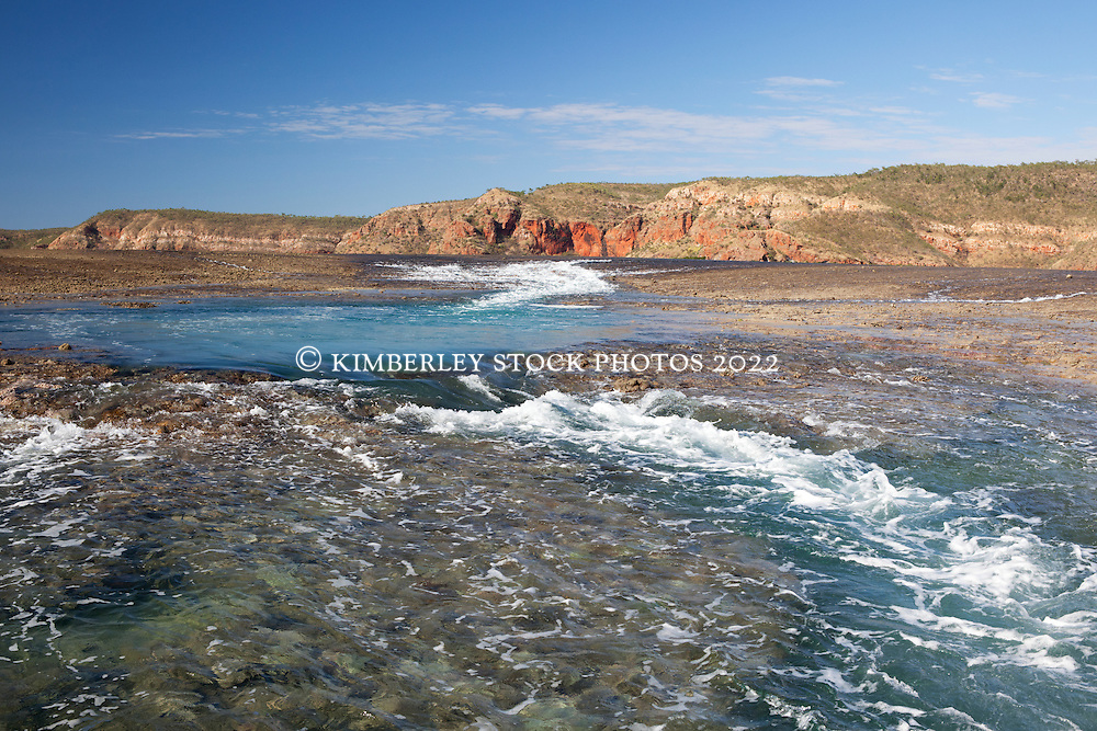 Water cascades off Turtle Reef in Talbot Bay.  The reef is one of the largest reef complexes on the lower Kimberley coast, joining Molema Island with the mainland.