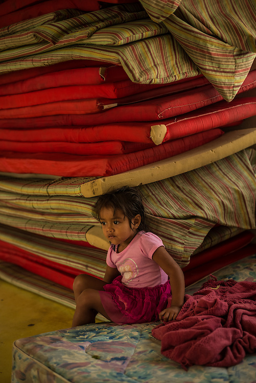 TENOSIQUE, MEXICO - JULY 2, 2014: Yisel Sondoval, 3, sits next to a stack of sleeping mats used by migrants at the 72 migrant shelter in Tenosique.  Yisel is traveling with her mother, trying to get to the United States, but her family has run out of money, so they have been at the shelter for 15 days trying to figure out what to do next.  PHOTO: Meridith Kohut for The New York Times