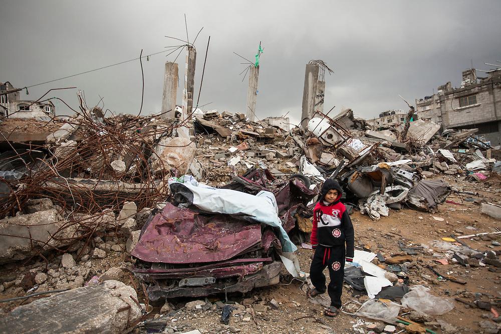 """Shejaya, quartiere a nord della striscia di Gaza. Una delle zone piu colpite dall'attacco israeliano """"Margine protettivo"""". Il quartiere è stato raso al suolo. La popolazione, a distanza di sei mesi dalla fine della guerra, vive tra le macerie della propria casa, al freddo, senza luce, gas e acqua. Nella foto un bambino tra le macerie delle case, detriti, elettrodomestici e macchine completamente distrutti che dalla fine della guerra nessuno ha mai rimosso."""
