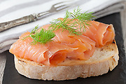 Smoked salmon with fresh dill on bread slice, in natural light, authentic food.
