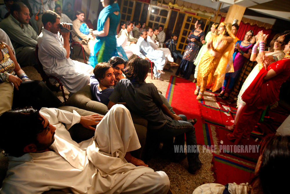 "Local men watch Hijras (eunuchs) perform at an underground party, June 16, 2005, Rawalpindi, Pakistan. The suspected hideout of Osama Bin Laden, Al Qaeda leaders and countless Islamic militants, Pakistan is also home to one of the subcontinents largest communities of transsexuals, eunuchs and transvestites, or as they are more commonly known - Hijras. Caught between modernity and fundamentalism at the frontline in the war against terror, the Islamic Republic is a country at war with its own identity, yet its Kushras (Urdu for eunuch) stand out as a tight-nit community of devout Muslims. As Pakistan's most marginalised community, they live in fear ""24 hours a day"", according to the group She-male Rights of Pakistan. Hijras are considered by many as unclean, amoral, drug users, and who also have the ability to place curses. Many people fear their curse so gravely, they will give generously when a Kushra comes to beg in their neighbourhood and ask them for Allah's blessing.. (Photo by Warrick Page)"