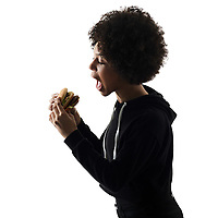 one mixed race african young teenager girl woman eating hamburger in studio shadow silhouette isolated on white background