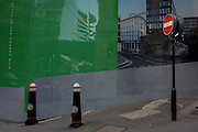Present-day No Entry and traffic bollards sign interacting with the background of a hoarding featuring a future building being constructed in the City of London.