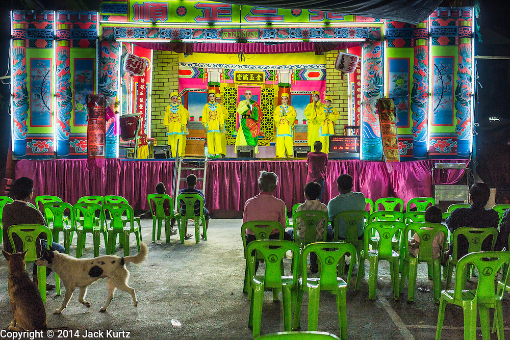 "25 JANUARY 2014 - BANG LUANG, NAKHON PATHOM, THAILAND: A Chinese opera performance in a small town near Bang Luang, Nakhon Pathom, Thailand. Chinese opera was once very popular in Thailand, where it is called ""Ngiew."" It is usually performed in the Teochew language. Millions of Chinese emigrated to Thailand (then Siam) in the 18th and 19th centuries and brought their cultural practices with them. Recently the popularity of ngiew has faded as people turn to performances of opera on DVD or movies. There are still as many 30 Chinese opera troupes left in Bangkok and its environs. They are especially busy during Chinese New Year when travel from Chinese temple to Chinese temple performing on stages they put up in streets near the temple, sometimes sleeping on hammocks they sling under their stage.     PHOTO BY JACK KURTZ"