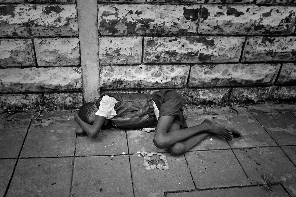 A young boy asleep on the streets of the capital.