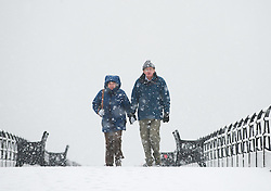 © Licensed to London News Pictures. 14/01/2013..Saltburn Pier , Cleveland, England..A couple walk along the Victorian pier at Saltburn by the Sea in Cleveland as parts of North Yorkshire and East Cleveland saw heavy snow fall today...Photo credit : Ian Forsyth/LNP