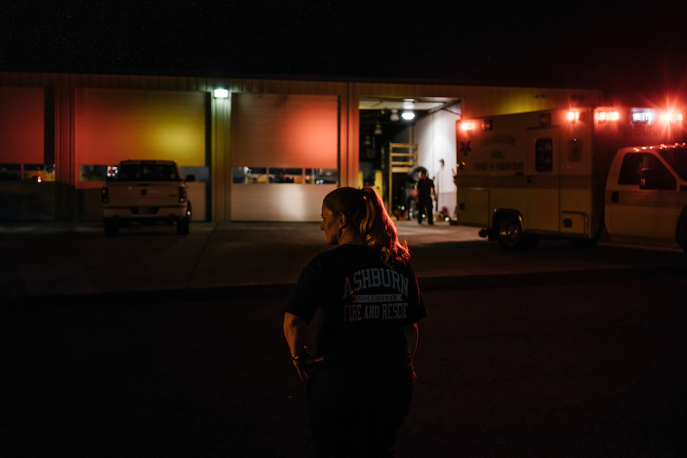 Heidi Wallner, firefighter, National Registry emergency medical technician, and safety supervisior for LSG Sky Chefs, waits outside the station during downtime on her overnight shift in Ashburn, Virginia on Sept. 23, 2015. Wallner is a volunteer, working one night a week with other EMTs.